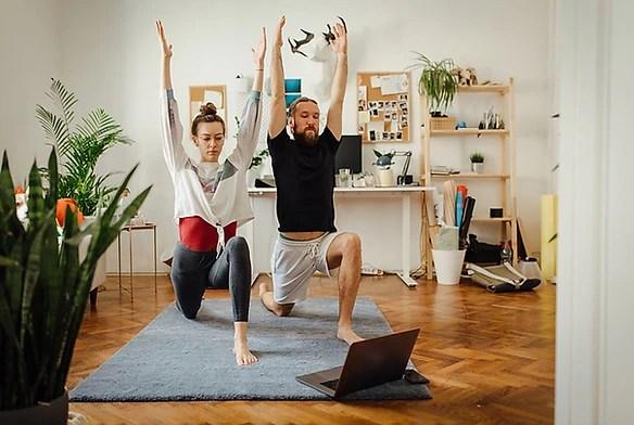Pareja siguiendo una clase de yoga en vivo