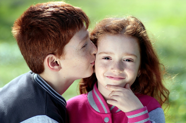 Young boy kissing a young girl on the cheek