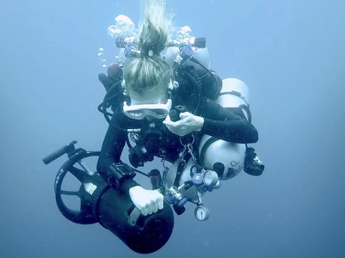 Underwater image of a blonde woman on a scientific dive, holding dive gear and scientific equipment.