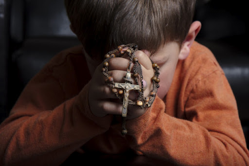 A child praying the rosary