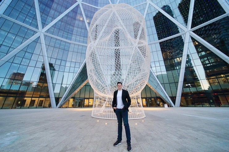 """Ken King stands in front of the """"Alice Head"""" in downtown Calgary, Canada."""