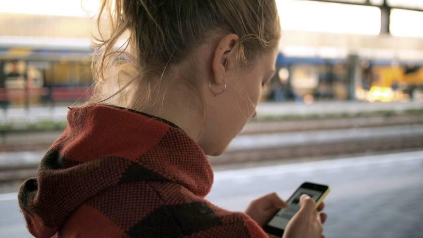 mulher loira de agasalho vermelho usa o celular enquanto aguarda metro