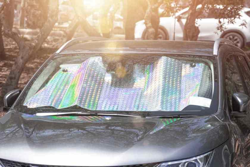 manta refeltiva no painel do carro em dia de sol