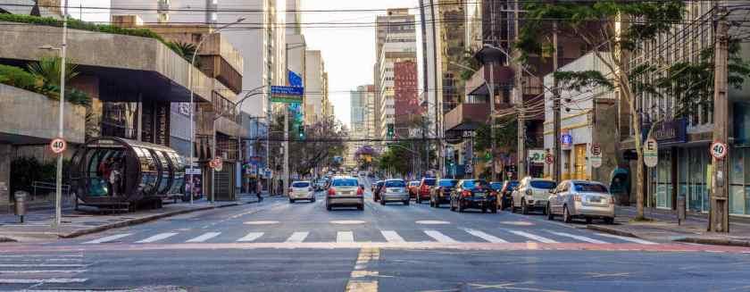 importante avenida em curitiba no centro com carros estacionados proximos a guia