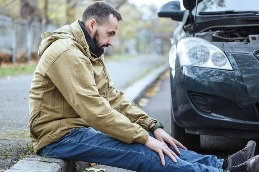 Motorista sentado na calçada em estado de choque após acidente com o carro