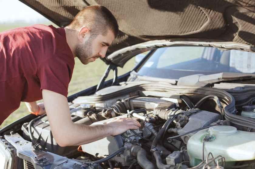 homem checa o motor do seu carro com capô aberto