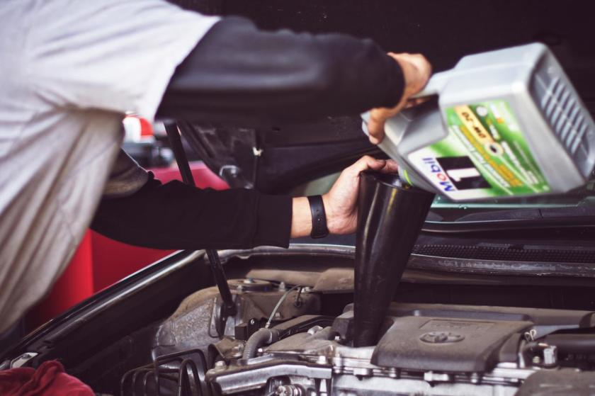 mecânico troca óleo do motor de carro em oficina mecânica