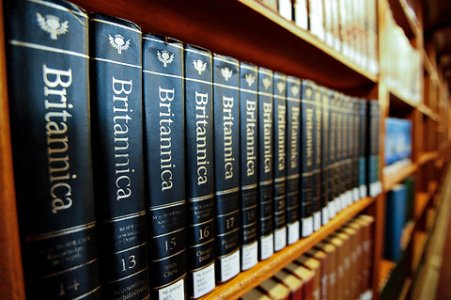 This is an image of a book shelf that has several Britannica dictionaries lined across the shelf.