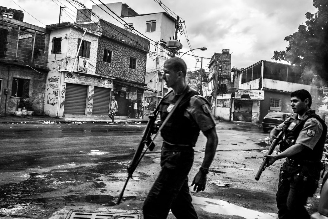Police officers patrolling the streets of Vila Cruzeiro, another favela in Rio, near where a motorbike taxi driver was killed hours earlier. Credit Sebastián Liste/Noor Images, for The New York Times