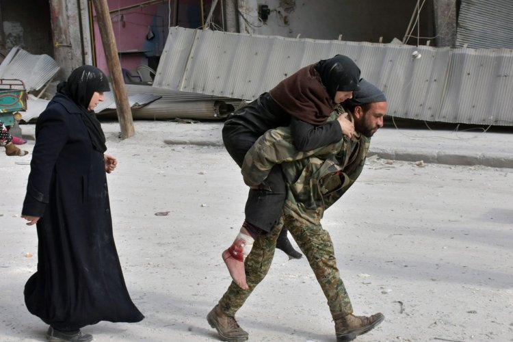 A government soldier carried an injured woman on Tuesday. CreditSana/European Pressphoto Agency