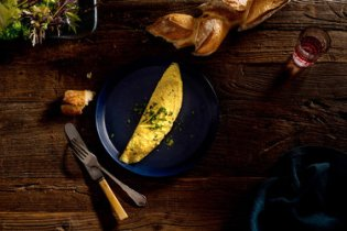 A dish of beaten eggs that are cooked in a skillet with butter, then folded for a firm exterior and tender curds within.
