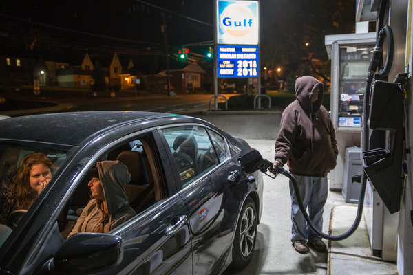 Service Attendant Pumping Gasoline Into Ford Sedan As Woman Watches At Gas Pumps