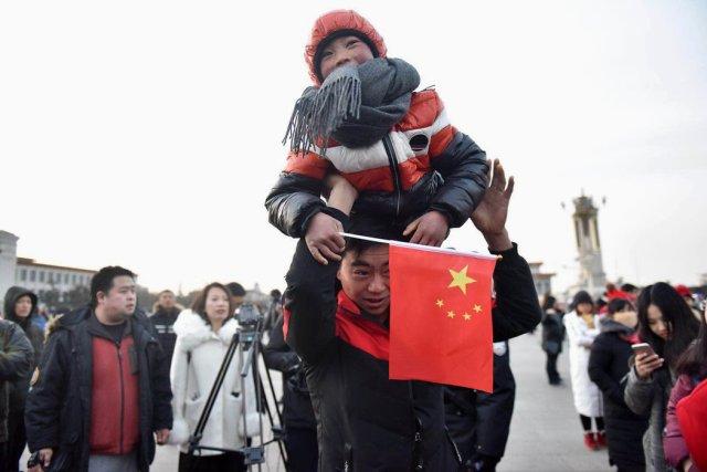 周六,8岁的王福满和他的父亲一起观看北京天安门广场升旗仪式。中国官方新闻媒体没有错过这个时刻。