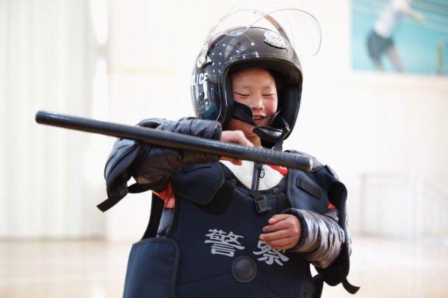 周六,王福满在北京穿着防暴装备玩耍。