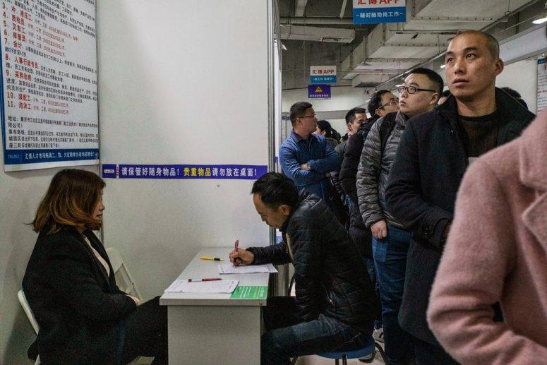 上个月,在中国重庆的一个人才市场上,一名男子正在填写一份申请表。