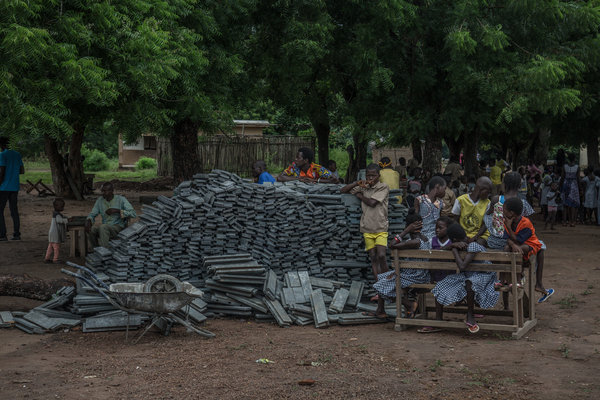Students and residents gathered by plastic bricks outside their school in the Sakassou village.