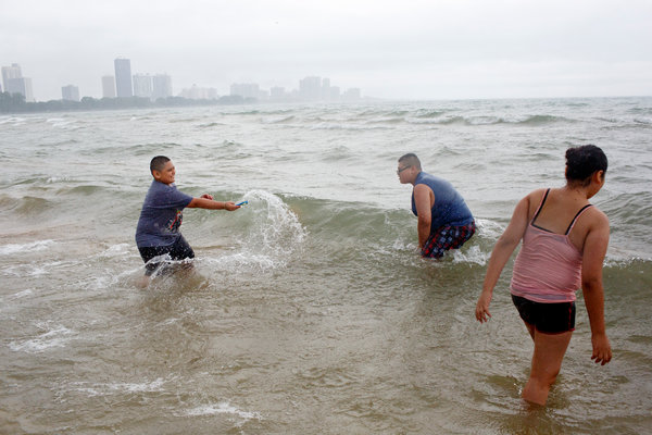 From left, Anthony Delgato, 10; Ruviel Delgato, 13; and Jellyxia Delgato, 12; play in the waves at Montrose Beach in Chicago on Sunday.