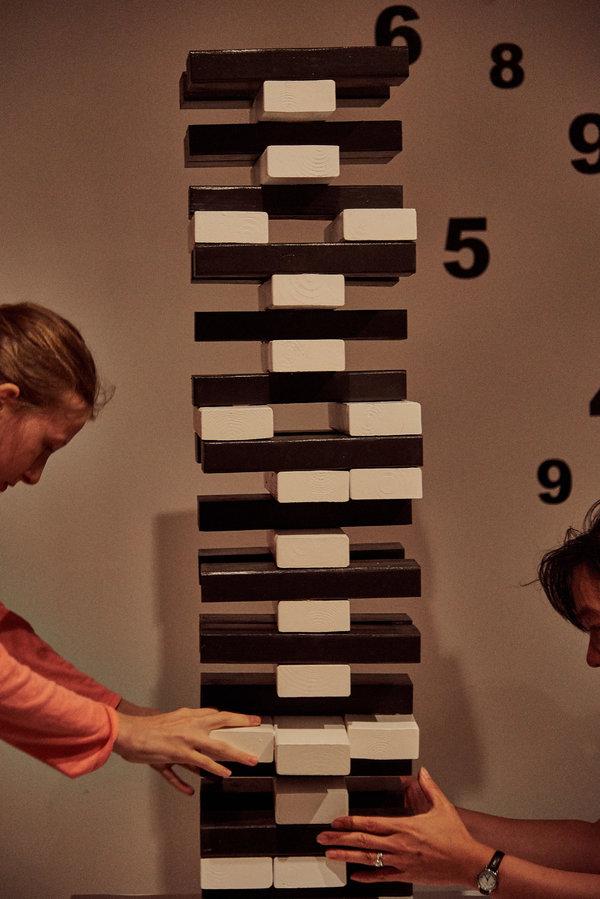 Les joueurs tirent des blocs d'une tour semblable à Jenga.