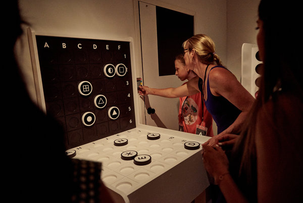 Les participants essaient un code sur l'une des portes de la salle d'échappement.  Chaque groupe se bat contre la montre pour résoudre une série de puzzles interactifs qui ressemblent à des jeux de société populaires.