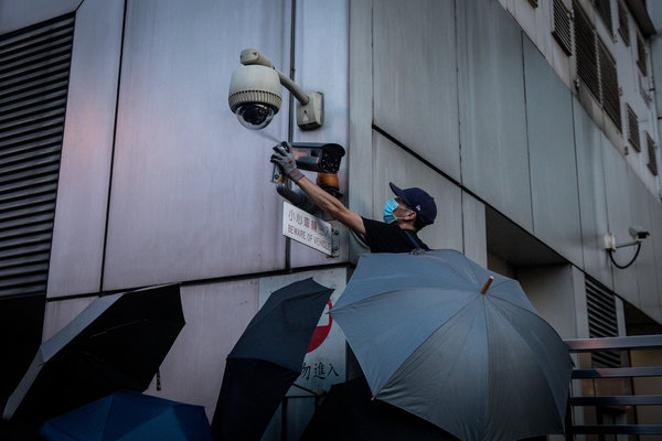 A protester spray-painted a security camera outside the Chinese government's liaison office in Hong Kong this week. As the protests have intensified, faces and identities have become potent weapons on both sides.