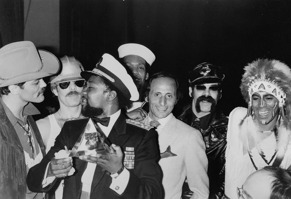 "Henri Belolo — he's the one without a costume — with the Village People in an undated photograph. Mr. Belolo and the composer Jacques Morali, a business partner, created the group in 1977 after, he recalled, they ""started to fantasize on what were the characters of America."""