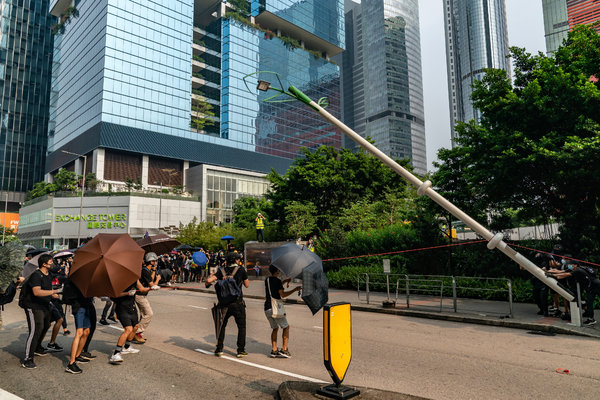 Protesters pulling down a smart lamppost during an anti-government rally in August.