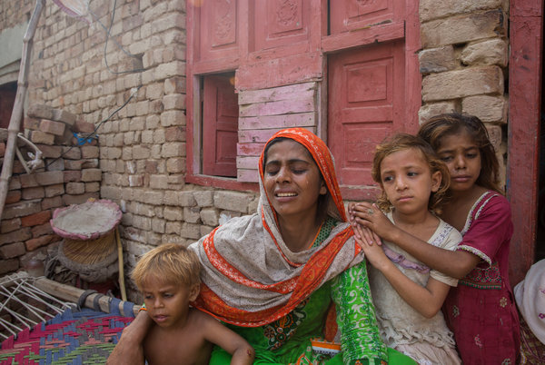 Ghazala Bibi, center, with her three remaining children. Her 9-year-old son, Ali Husnain is believed to have been killed by the same person who killed Muhammad Faizan.