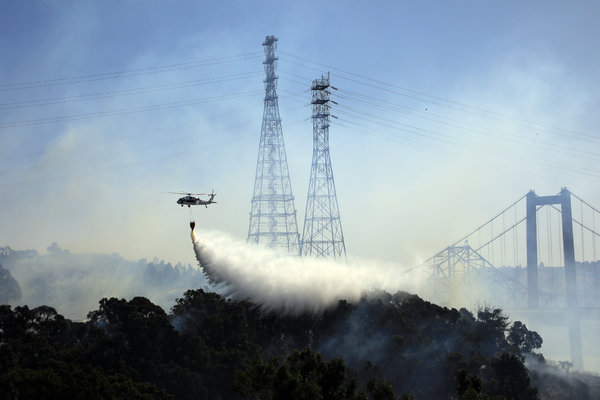 A helicopter dropped water on a smoldering fire near the Carquinez Bridge in Vallejo, Calif., on Sunday. High winds apparently blew burning embers a mile across the Carquinez Strait to start a fire on the far side.