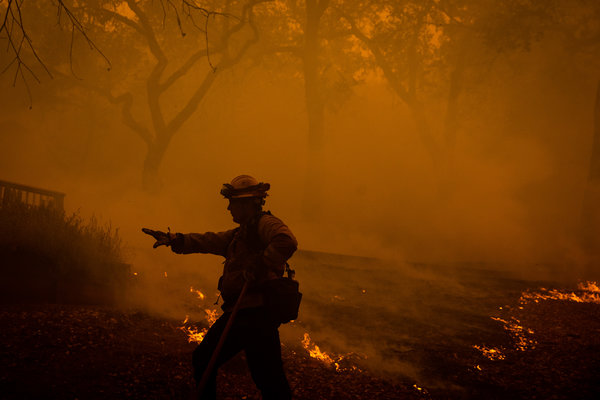 More than 3,000 firefighters were at work battling the Kincade fire in Northern California on Sunday. One firefighter dug a containment line around a house as the fire burned into the city of Windsor.