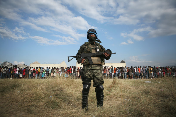 A United Nations peacekeeper stood guard in 2010 as residents of Cité Soleil in Haiti lined up for food and supplies after being displaced by an earthquake.