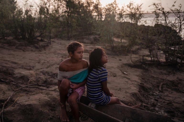 Chicas esperando a que los pescadores lleguen con una captura que puedan llevarse a casa.Crédito...Adriana Loureiro Fernandez para The New York Times