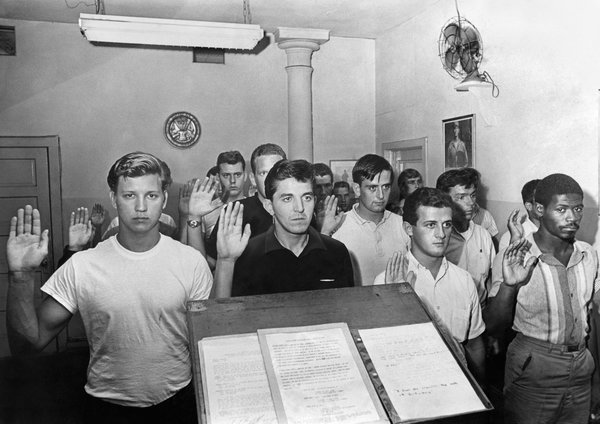 Army inductees pledged their service in New York City in 1965, while protesters burned draft cards and shouted antiwar slogans outside. The draft was abolished in 1973.