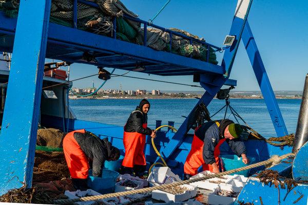 Pescatori nel Mare Piccolo con l'acciaieria sullo sfondo.