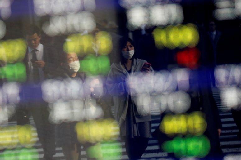 周四,带着口罩的东京居民走过一个显示股价的广告牌。