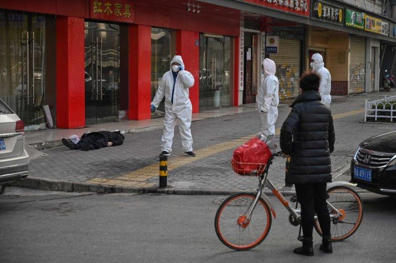 """周四,一名老者在武汉一家医院附近倒地死亡。尚不清楚是否是因为冠状病毒。""""那些能够被诊断和治疗的人运气好,""""一名居民说。"""