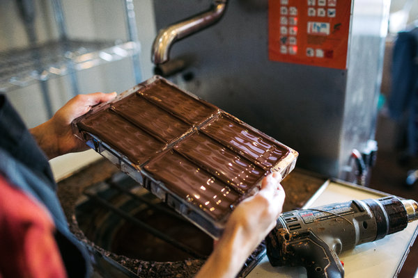 After tempering, the liquid chocolate is poured into molds, then allowed to set. Finished bars should be glossy, and snap when you break off a piece.