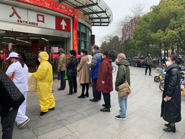 Residents lining up to enter a supermarket in Wuhan, China, on Tuesday. The city, the center of the outbreak, limits the number of people allowed to enter at the same time.