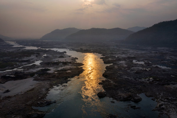 A narrow section of water flows through mud and pools in the dried out river bed of the Mekong River near Sangkhom.