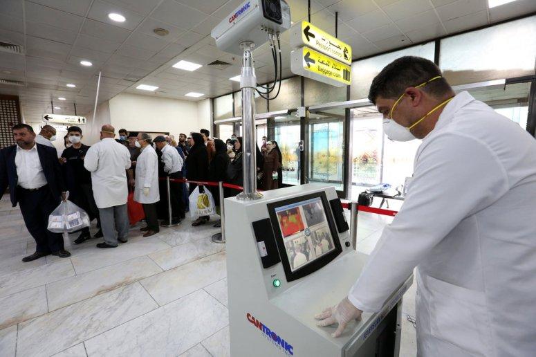医务人员正在检查从伊朗抵达巴格达国际机场的乘客的体温。