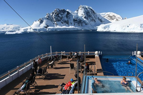 Tourists look at glaciers onboard the Hurtigruten hybrid expedition cruise ship MS Roald Amundsen at Chiriguano Bay in Antarctica.
