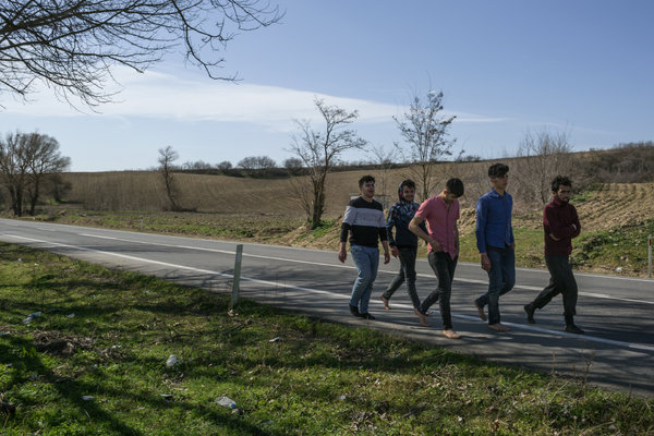 A group of Syrians walking barefoot on a highway in northwestern Turkey after being sent back by Greek border guards. They said they had been detained and beaten in Greek government facilities.