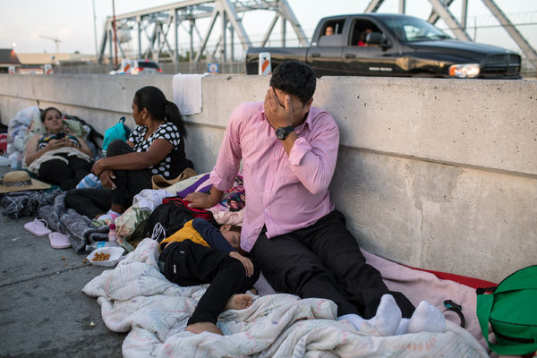 A Honduran man and his son on the Mexican side of the border after being denied entry into the United States.