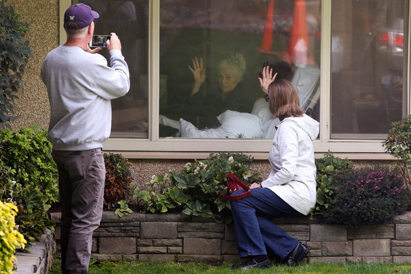 Lori and Michael Spencer, foreground, visited Lori's mother, Judie Shape, who Lori said had tested positive for coronavirus, at the Life Care Center of Kirkland, Wash., on Wednesday.