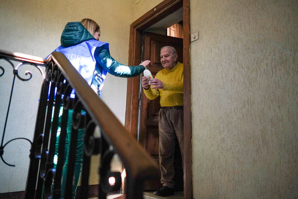 A volunteer with the Community of Sant'Egidio, a humanitarian organization, delivered milk to Lamberto Paolucci, 88, in Rome earlier this month.