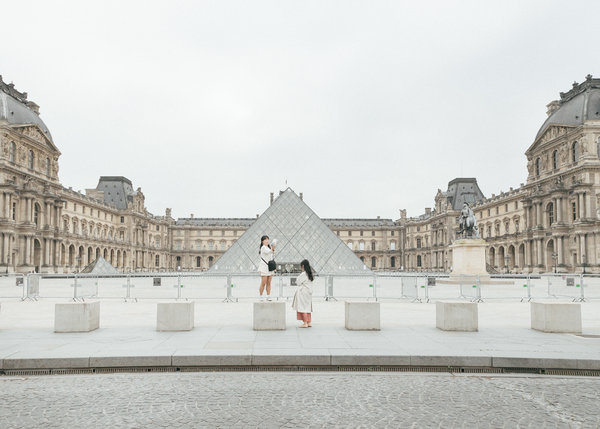 Taking pictures at the Louvre in Paris on Tuesday, just before France's nationwide lockdown began.