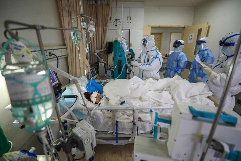 3月初,中国武汉红十字医院的医务人员检查一名冠状病毒患者。