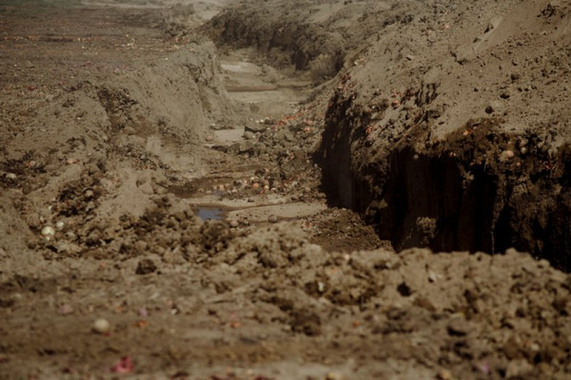 Um poço cavado para descartar as cebolas não utilizadas.  As cebolas serão deixadas apodrecer no solo.