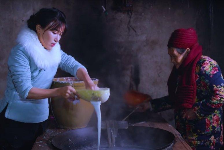 李子柒用红薯提取淀粉做成面糊,制作传统粉条,然后在祖母帮助下过滤,放进沸水中。