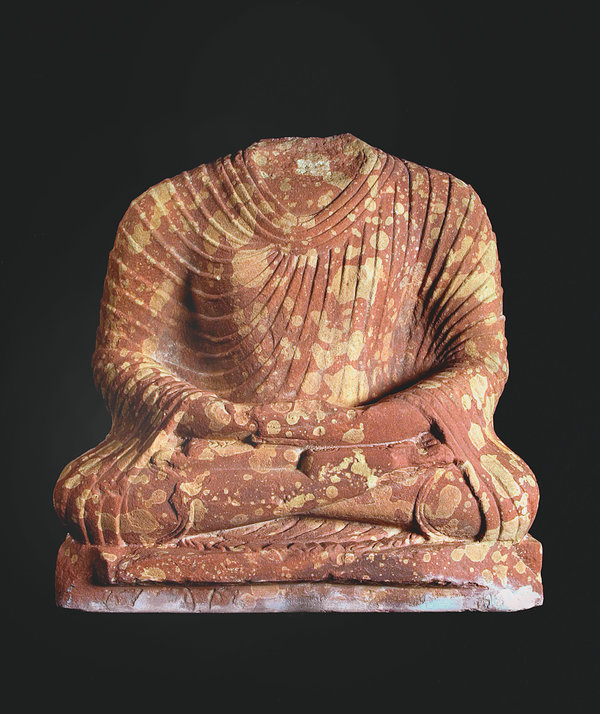 A headless seated Buddha, from approximately A.D. 200 to 300, made in Mathura, in what is now central India. Mathura was one of the earliest and most important sites for the development of the Buddha's image. Artisans there often worked in red sandstone with white spots.