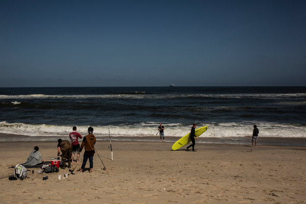 A surfer and fishermen in Sandy Hook, N.J.